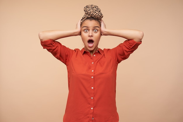 Giovane donna castana elegante scioccata con trucco naturale che stringe la testa con le mani alzate mentre guarda stordito davanti, isolato sopra il muro beige