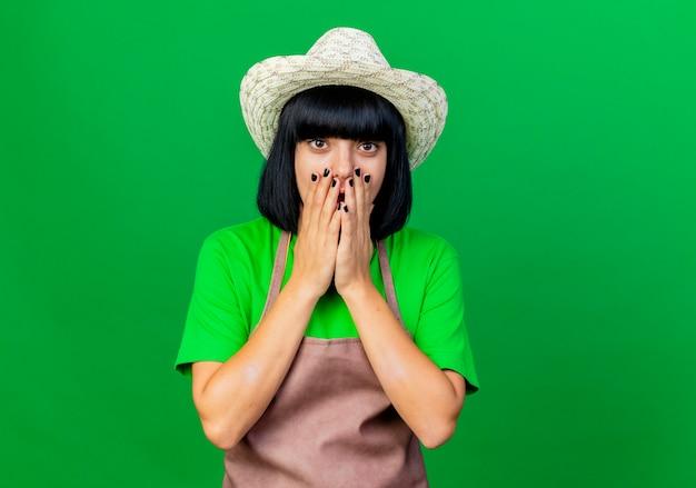 Il giovane giardiniere femminile scioccato in cappello da giardinaggio d'uso uniforme mette le mani sulla bocca alla ricerca