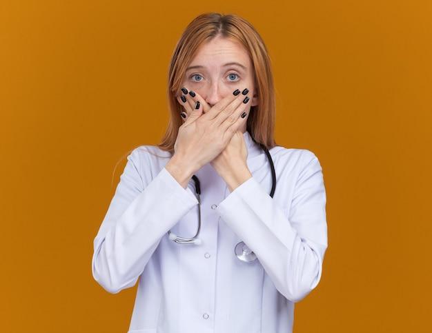 Scioccata giovane dottoressa allo zenzero che indossa una tunica medica e uno stetoscopio che tiene le mani sulla bocca isolata sulla parete arancione