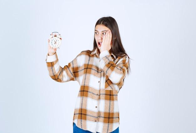 Шокированная модель молодой девушки держит будильник.