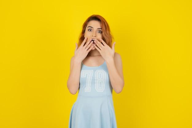 Шокированная молодая девушка на желтой стене