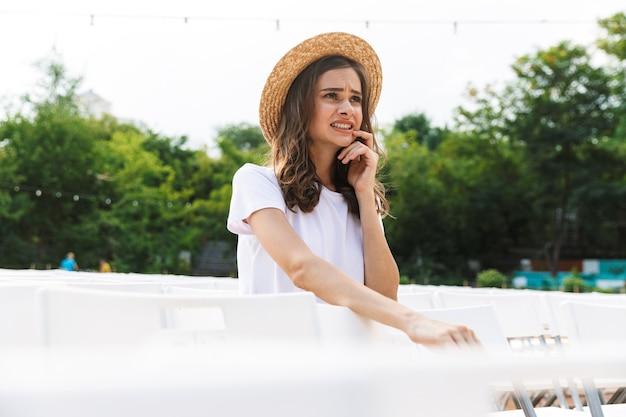 여름에 야외 도시 공원에 앉아 충격 된 어린 소녀