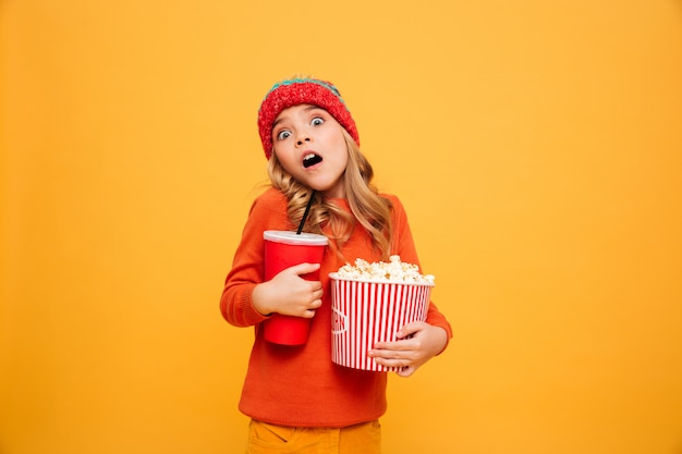 Shocked young girl in sweater and hat holding popcorn and plastic cup while looking at the camera over orange