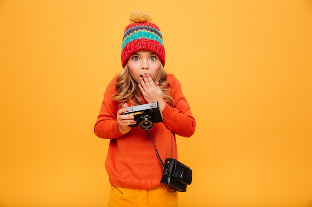 Shocked young girl in sweater and hat holding retro camera and looking at the camera over orange