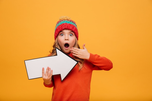 Shocked young girl in sweater and hat pointing with paper arrow away and looking at the camera over orange