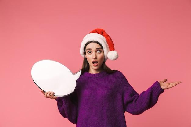 빈 연설 거품을 들고 핑크 이상 격리 서 빨간 산타 모자를 쓰고 충격 된 어린 소녀