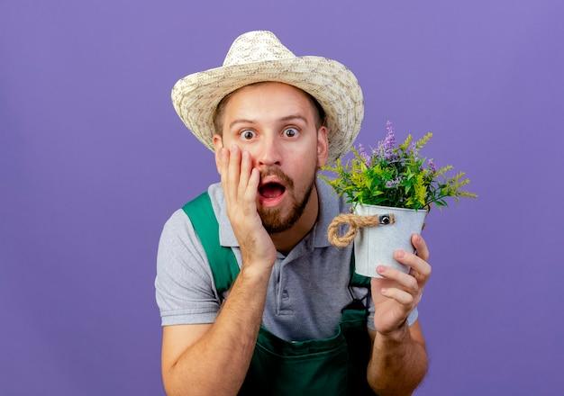 Giovane giardiniere slavo bello scioccato in uniforme e cappello che tiene il vaso da fiori che tocca il fronte isolato sulla parete viola con lo spazio della copia