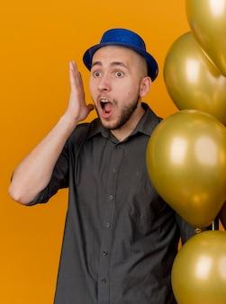 오렌지 배경에 똑바로 찾고 머리 근처에 손을 유지 풍선을 들고 파티 모자를 쓰고 충격 된 젊은 잘 생긴 슬라브 파티 남자