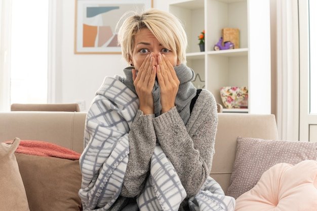 Shocked young ill slavic woman with scarf around her neck wrapped in plaid putting hands on mouth sitting on couch at living room