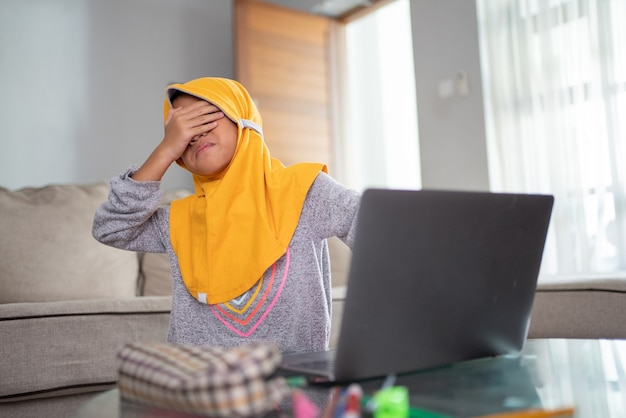 집에서 랩톱 컴퓨터를 사용하는 동안 충격을받은 어린 아이가 눈을가립니다.