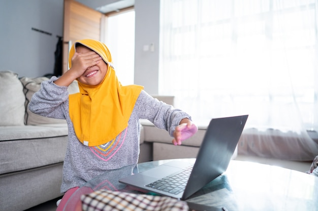 Shocked young kid cover her eyes while using laptop computer at home
