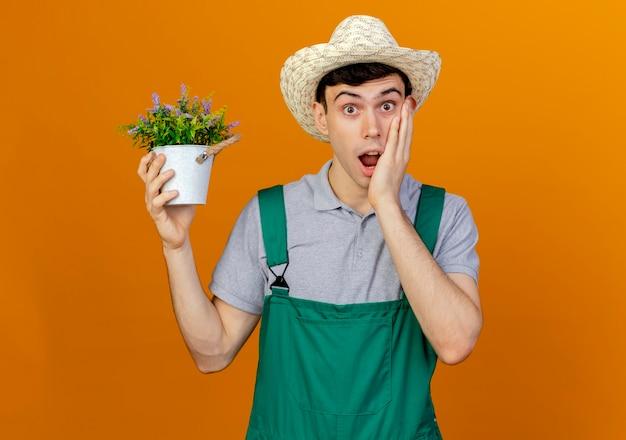 Шокированный молодой мужчина-садовник в садовой шляпе держит горшок и кладет руку на лицо