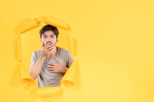 찢어진 노란 종이 배경에 충격을 받은 젊은 남성 얼굴 실내 남자 잘생긴