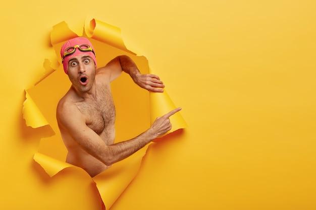 Il giovane nuotatore maschio scioccato posa con il torso nudo, indossa il costume da bagno rosa e gli occhiali protettivi, indica lo spazio libero