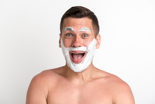 Shocked young man applied shaving cream on beard and eyebrow
