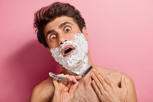 Shocked young man applies foam, prepares for trimming beard, holds razor blader, feels thick and tired of daily shaving