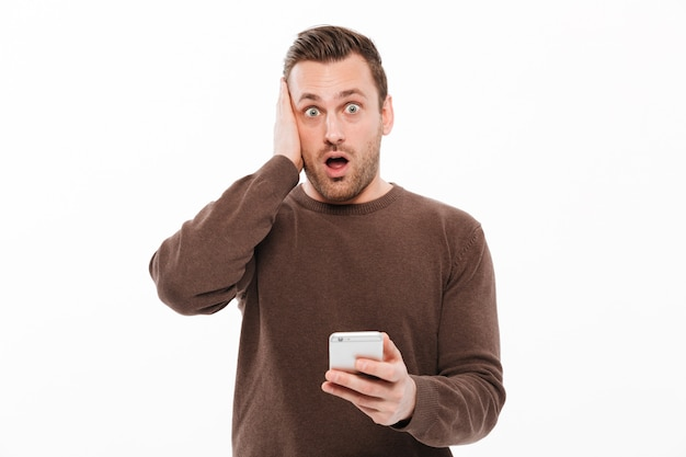 Shocked young man chatting by mobile phone