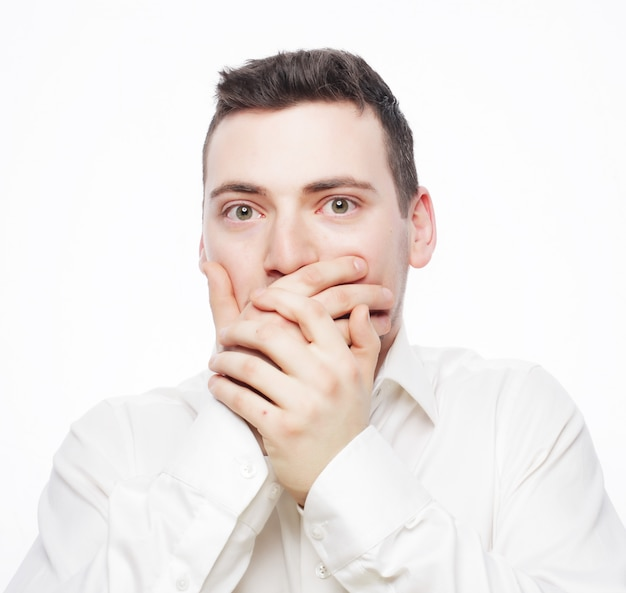 Shocked young man covering mouth with hands