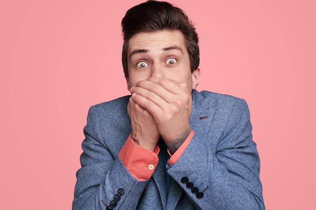 Шокирован молодой человек, закрывающий рот