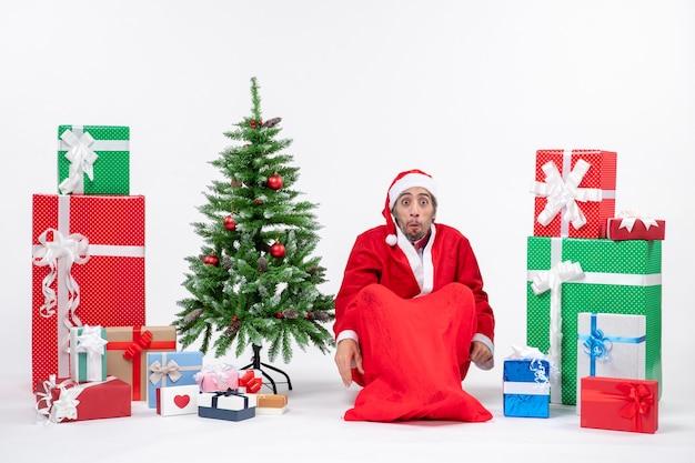 Giovane scioccato vestito da babbo natale con doni e albero di natale decorato seduto per terra su sfondo bianco