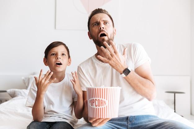 Шокированный молодой человек, отец, папа, смотрит телевизор, ест попкорн.