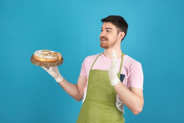 Giovane scioccato che tiene in mano una fetta di torta fresca e la guarda.