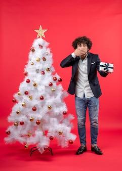 Giovane scioccato che tiene il suo regalo e chiude la bocca in piedi vicino all'albero di natale bianco decorato sul lato destro del rosso