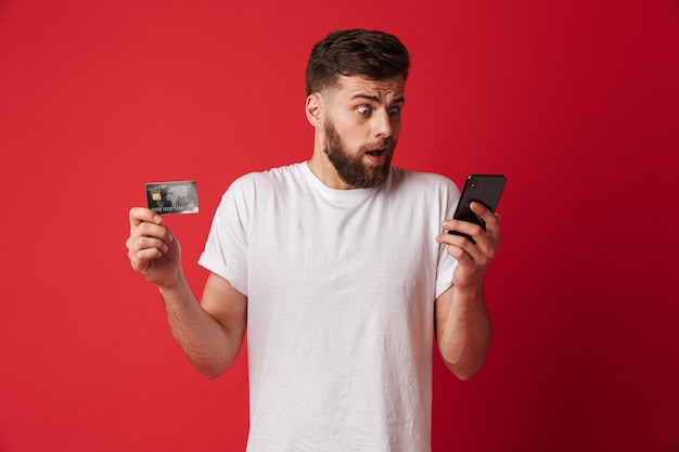 Shocked young man holding mobile phone and credit card. looking aside.