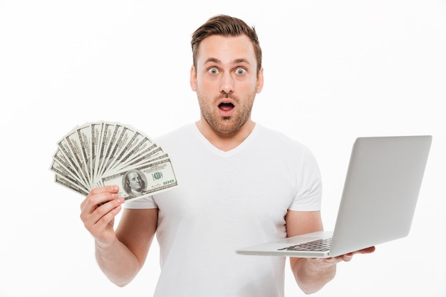Shocked young man holding money using laptop computer.