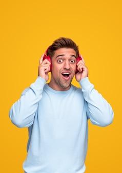 Шокированный молодой человек в синей толстовке поправляет наушники и смотрит в камеру с открытым ртом, слушая громкую музыку на желтом фоне