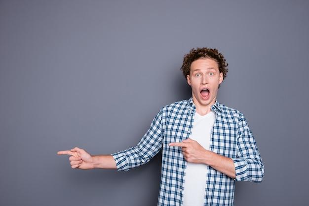 2本の指を脇に向けるカジュアルな市松模様のシャツを着たショックを受けた若い男