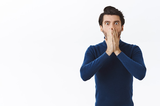 Shocked young man losing lots money, failed business meeting, hold hands on mouth, stare speechless and concerned, gasping worried, nervously react to terrible situation, white wall
