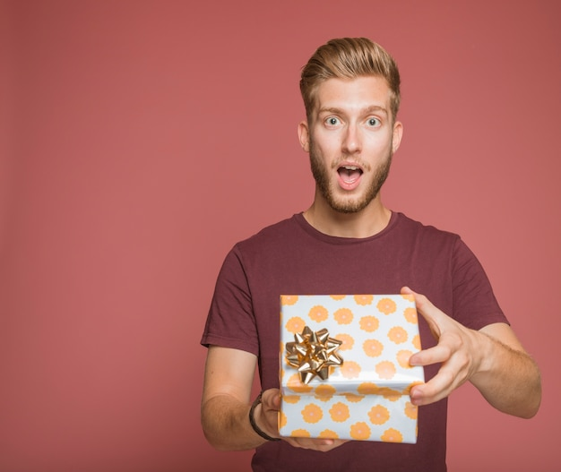 Shocked young man opening an floral gift box with golden bow