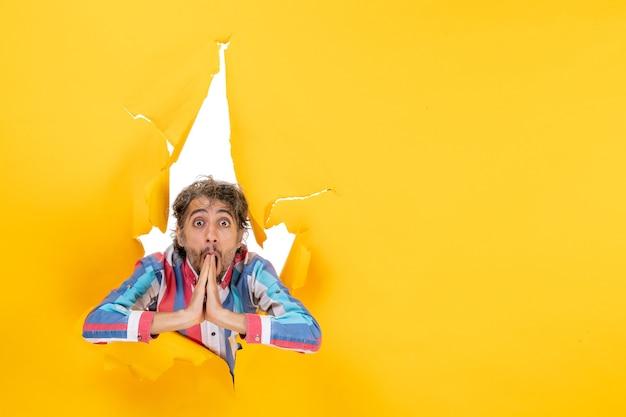 ショックを受けた若い男は、引き裂かれた黄色の紙の穴の背景でポーズをとる