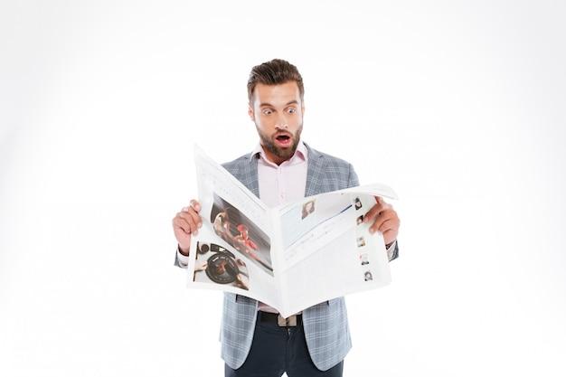 Shocked young man reading gazette.