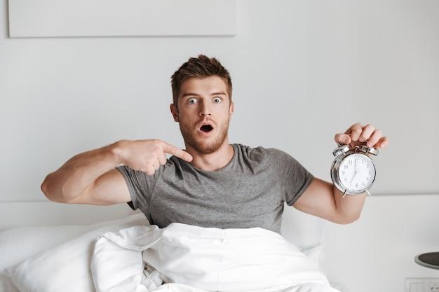 Шокирован молодой человек показывает будильник, сидя в постели