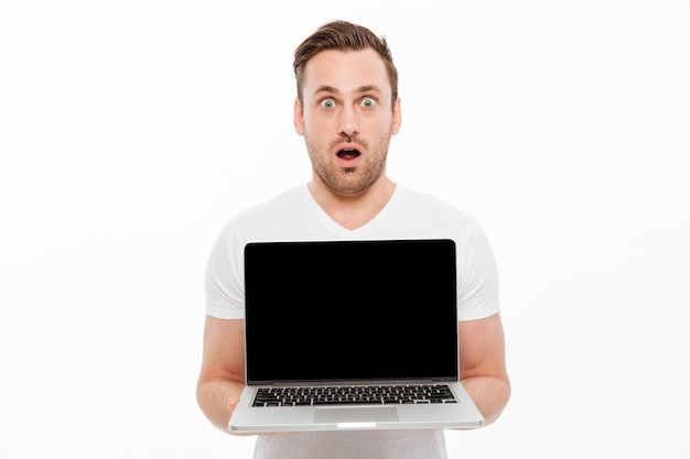 Shocked young man showing display of laptop.