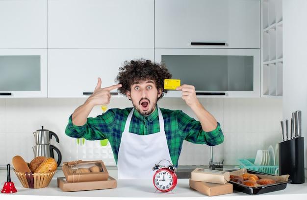 テーブルの後ろに立って、白いキッチンで銀行カードを見せているショックを受けた若い男