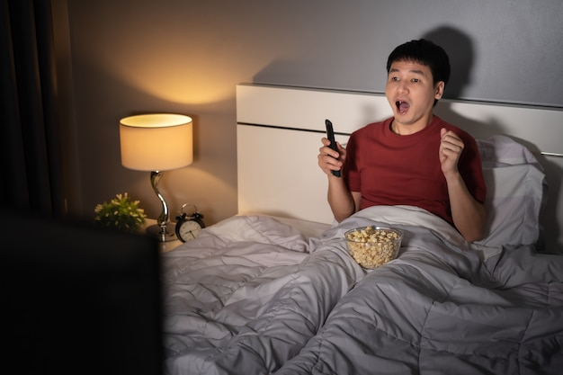 Shocked young man watching tv movie on a bed at night