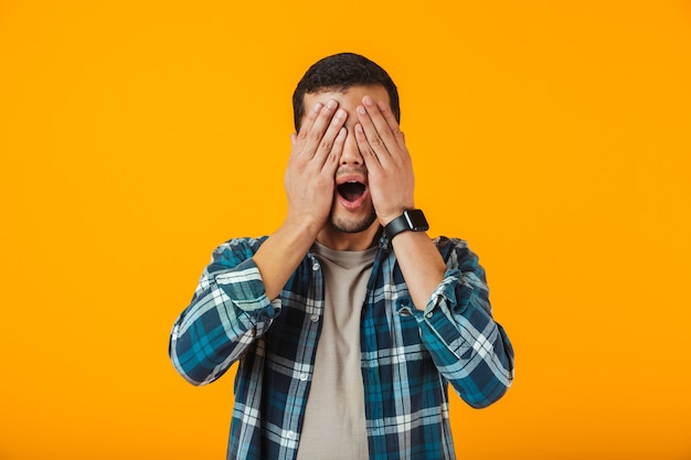 Shocked young man wearing plaid shirt standing isolated over orange wall, cover face