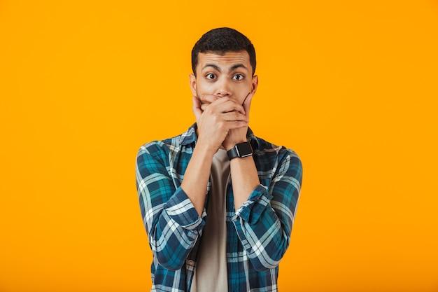 Шокированный молодой человек в клетчатой рубашке стоит изолированно над оранжевой стеной, прикрывая лицо