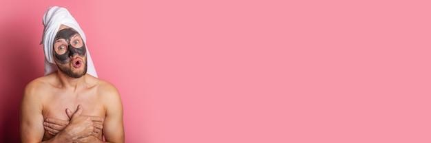 彼の顔に化粧マスクを持ってショックを受けた若い男は、ピンクの背景に彼の手で彼の裸の胸を覆います