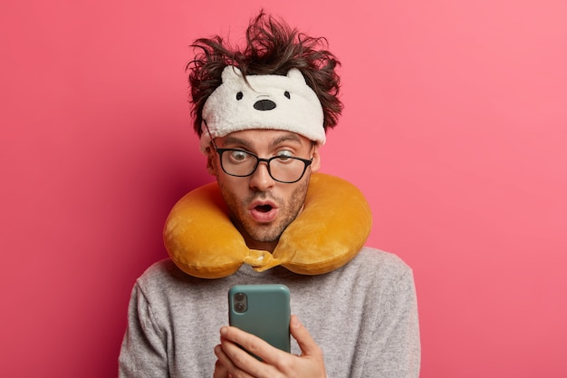 Giovane scioccato con i capelli disordinati fissa lo smartphone