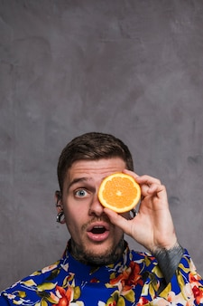 Shocked young man with pierced ears and nose holding and orange slice in front of eyes against grey wall