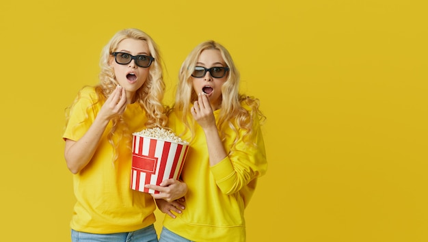 Shocked young models women in 3d glasses eating popcorn, looks scary movie. isolated on yellow wall