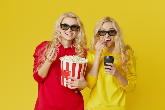 Shocked young models women in 3d glasses eating popcorn, looks scary movie . isolated on yellow wall