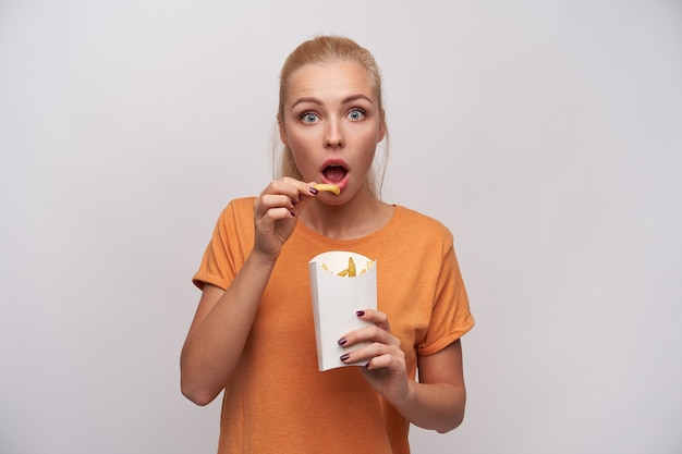 흰색 배경 위에 서있는 동안 제기 손에 감자 튀김을 유지, 넓은 입으로 카메라를 놀랍게보고 찾고 오렌지 티셔츠에 충격 젊은 예쁜 금발의 여자