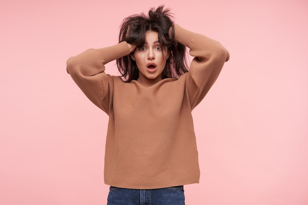 Shocked young pretty brunette lady keeping her hands raised while rumpling her hair and looking surprisedly at front with wide eyes opened, posing over pink wall