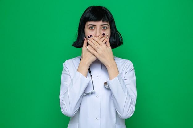 Scioccata giovane bella ragazza caucasica in uniforme da medico con uno stetoscopio che copre la bocca con le mani