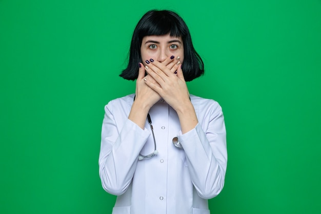 手で口を覆う聴診器で医者の制服を着たショックを受けた若いかなり白人の女の子